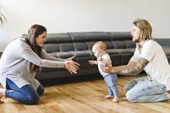 A filha do bebê da ajuda do pai para tomar primeiramente pisa em casa fotografia de stock
