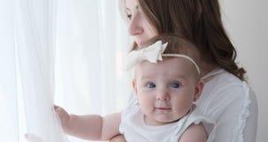 Filha do bebê da terra arrendada da mãe e vista para fora através da janela vídeos de arquivo