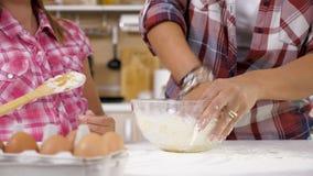 A filha e a mãe na cozinha amassam a massa filme