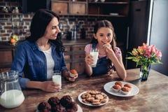 Filha e mãe que comem queques fotos de stock royalty free