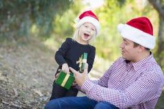 Filha entusiasmado que dá o pai A Christmas Gift Outdoors Imagens de Stock