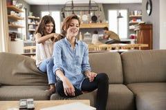 A filha escova o cabelo do ` s da mãe como eles Sit On Lounge Sofa fotografia de stock