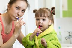 Filha feliz da mãe e da criança que escova seus dentes em casa no banheiro foto de stock royalty free