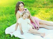 Filha feliz da mãe e da criança junto na grama Fotografia de Stock Royalty Free