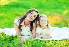 Filha feliz da mãe e da criança que encontra-se junto na grama no verão Fotos de Stock Royalty Free