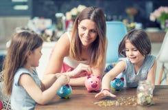 A filha feliz da mamã da família salvar economias do investimento do futuro do mealheiro do dinheiro imagem de stock