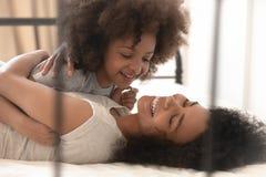 Filha feliz e mum da criança da misturado-raça que jogam o encontro na cama imagem de stock royalty free