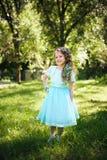 Filha feliz que sorri na câmera no parque do verão imagem de stock