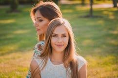 A filha feliz sorri, e atrás dela senta sua mãe Imagens de Stock Royalty Free