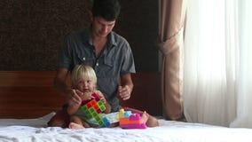 a filha loura pequena joga o construtor do brinquedo com pai filme