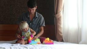 a filha loura pequena joga o construtor do brinquedo com pai video estoque