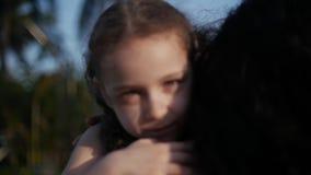 A filha nos braços da mãe na rua e dá-lhe um abraço grande, beijando e sorrindo filme