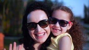A filha nos braços da mãe na rua e dá-lhe um olhar grande na câmera, fim do abraço, do beijo e do sorriso vídeos de arquivo