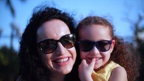 A filha nos braços da mãe na rua e dá-lhe um olhar grande na câmera, fim do abraço, do beijo e do sorriso filme