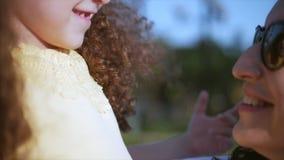 A filha nos braços da mãe na rua e dá-lhe um olhar grande na câmera, fim do abraço, do beijo e do sorriso video estoque