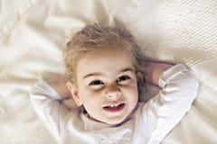 Filha nova dois anos de relaxamento velho na cama, sentimentos positivos imagem de stock royalty free