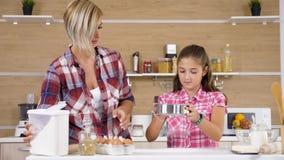 A filha nova peneira a farinha através de uma peneira na cozinha filme