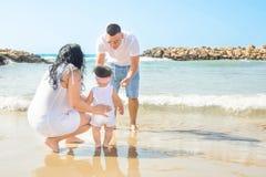 Filha pequena bonito da menina da criança do bebê do apoio novo da posse dos pais que aprende andar Luz solar azul do mar da prai foto de stock