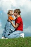 Filha pequena do beijo da matriz na grama verde fotos de stock royalty free