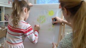 A filha pequena e sua mãe estão tirando com lápis coloridos video estoque