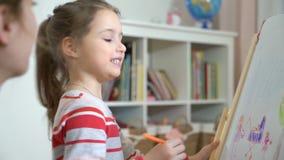 A filha pequena e sua mãe estão tirando com lápis coloridos filme