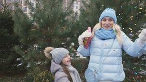 A filha pequena feliz e a mãe bonita com presentes exultam a um confete pequeno filme