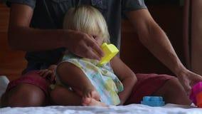 a filha pequena senta-se nos joelhos do pai para jogar brinquedos registra no sofá video estoque