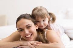 Filha que abraça sua mãe na cama branca Foto de Stock Royalty Free