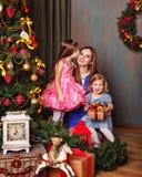 Filha que beija a mãe perto da árvore de Natal Imagens de Stock