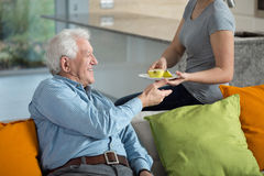 Filha que dá a maçã doente do vovô Fotografia de Stock