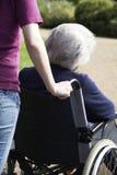 Filha que empurra a mãe superior na cadeira de rodas foto de stock