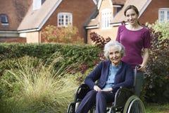 Filha que empurra a mãe superior na cadeira de rodas imagem de stock
