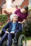 Filha que empurra a mãe superior na cadeira de rodas fotos de stock