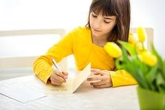 Filha que faz um cartão para sua mamã Imagens de Stock