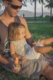 Filha que senta-se no regaço dos paizinhos Fotografia de Stock