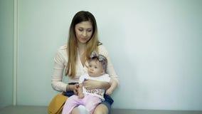 A filha senta-se em seu regaço perto de uma mãe bonita nova video estoque