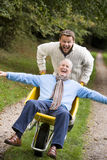 Filho acima crescido que empurra o pai no wheelbarrow foto de stock royalty free