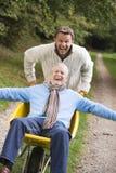 Filho acima crescido que empurra o pai no wheelbarrow fotografia de stock