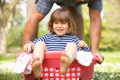 Filho carreg do pai que senta-se na cesta de lavanderia foto de stock royalty free