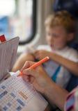 Filho com a mãe que joga um jogo da batalha de mar durante a viagem do trem Imagens de Stock Royalty Free