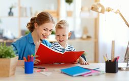 Filho da mãe e da criança que faz a escrita dos trabalhos de casa e que lê em casa fotos de stock royalty free