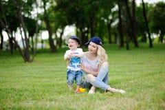 Filho da mamã e do bebê no tampão em um fundo da grama verde Foto de Stock