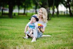 Filho da mamã e do bebê no tampão em um fundo da grama verde Fotografia de Stock