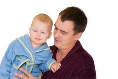 Filho da preensão do pai do sorriso que veste o bathrobe imagem de stock