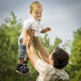 Filho da terra arrendada do pai no ar Foto de Stock Royalty Free