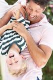 Filho da terra arrendada do pai upside-down ao ar livre Imagem de Stock Royalty Free