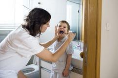 Filho de ajuda da mãe para escovar seus dentes imagens de stock royalty free