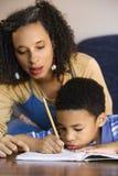 Filho de ajuda da mamã com trabalhos de casa fotografia de stock royalty free