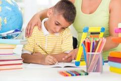 Filho de ajuda da mãe para fazer seus trabalhos de casa Fotografia de Stock Royalty Free