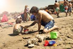 Filho de ajuda do pai com castelos da areia Fotografia de Stock